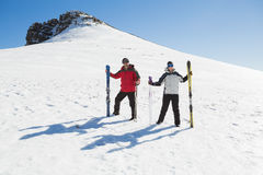Full length of a couple with ski boards standing on snow Stock Photography