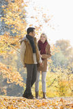 Full length of couple walking in park during autumn Stock Images
