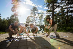 Full Length Of Coworkers Solving Crossword Puzzle In Forest. Full length of male and female coworkers solving crossword puzzle on patio in forest royalty free stock photos