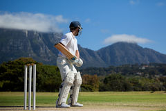 Full length of cricket player practicing against blue sky royalty free stock photography