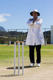 Full length of cricket umpire signaling cancel call sign during match. Against blue sky on sunny day royalty free stock photography