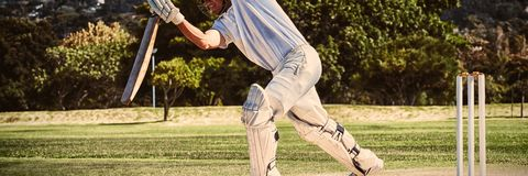Full length of cricketer playing on field. During sunny day royalty free stock photos
