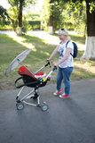 Full length of curvy mother looking into baby carriage in park Royalty Free Stock Photography