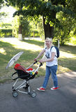 Full length of curvy mother walking with baby carriage in park Royalty Free Stock Photos