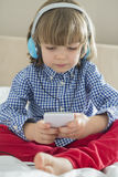 Full length of cute boy listening music on headphones in bedroom Royalty Free Stock Images