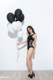 Full length of a cute half-naked dancer holding balloons Stock Photo