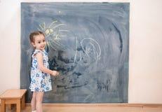 Full length cute little girl standing near blackboard Stock Images