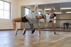 Full length of dancers practicing against mirror on floor. Full length of dancers practicing against mirror on wooden floor at studio stock images