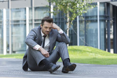 Full length of depressed businessman sitting on path outside office Royalty Free Stock Images
