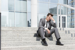 Full length of depressed businessman sitting on steps outside office Royalty Free Stock Photography