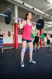 Determined Female Lifting Heavy Barbell. Full length of determined female lifting heavy barbell in gym Stock Image