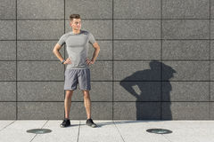 Full length of determined jogger standing against tiled wall outdoors Royalty Free Stock Images