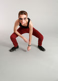 Full length edgy male model. Crouching male fashion model with makeup Royalty Free Stock Photo