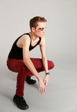 Full length edgy male model. Crouching male fashion model with makeup Royalty Free Stock Images