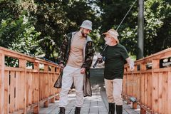 Full length of elderly angler and son standing on the wooden bridge. Pleasant aged fisherman walking along the bridge with his son while having a lively talk stock photography