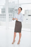 Full length of an elegant businesswoman with clipboard in office Stock Photos