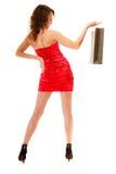 Full length of elegant girl in red dress with black shopping bag Royalty Free Stock Image
