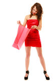 Full length of elegant girl in red dress looking into shopping bag Royalty Free Stock Photo