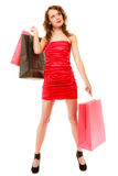 Full length of elegant girl in red dress with shopping bags Royalty Free Stock Image