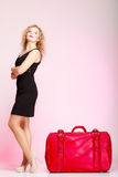 Full length elegant lady in voyage, traveler woman with old red bag. Full length of young elegant lady in voyage, traveler woman with old red suitcase luggage Stock Photo