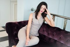Full length of an elegant young woman sitting with head in hands on sofa at home royalty free stock image