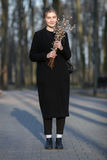 Full length emotional portrait of young happy beautiful woman with a bouquet of pussy-willows wearing black coat strolling at even Stock Image