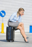 Full length of exhausted businesswoman sitting on luggage Stock Photography