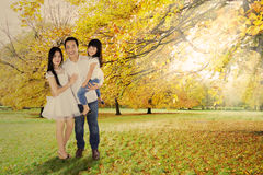 Full length of family under autumn tree Royalty Free Stock Images