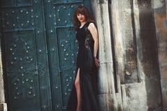 Full-length fashion model in black dress posing in the street ne Stock Photo