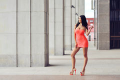 Full length fashion portrait of beautiful woman in red dress posing in the city.  stock photo