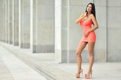 Full length fashion portrait of beautiful woman in red dress posing in the city.  stock photos