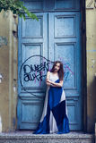 Full length fashion portrait modern woman standing near old door royalty free stock image