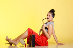 Full length fashionable pin-up girl with glasses and bun on yellow Stock Photos