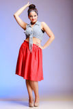 Full length fashionable pin-up girl woman with bun on violet Stock Photos