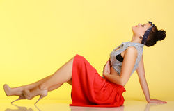 Full length fashionable pin-up girl woman with bun on yellow Royalty Free Stock Images