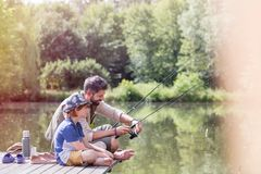 Full length of father assisting son fishing in lake while sitting on pier stock image