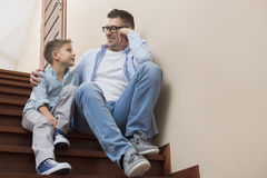 Full length of father and son looking at each other while sitting on steps at home Royalty Free Stock Photography