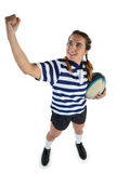 Full length of female athlete holding rugby ball while standing with clenching fist Stock Photo