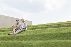 Full length of female business executives with disposable coffee cup and laptop sitting on grass steps against sky Stock Images