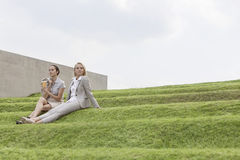 Full length of female business executives sitting on grass steps against sky Stock Photography