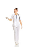 Full length female doctor pointing to the left Royalty Free Stock Image