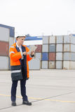 Full-length of female engineer using tablet computer in shipping yard Royalty Free Stock Photo
