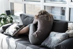 Sorrowful young woman sitting on sofa. Full length female expressing sadness while leaning on cozy couch. She turning back to camera Stock Image