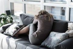Sorrowful young woman sitting on sofa Stock Image