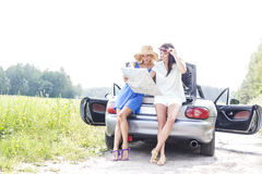 Full length of female friends reading map while leaning on convertible in countryside Royalty Free Stock Images