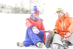 Full length of female friends with snowboard relaxing during winter Royalty Free Stock Photo