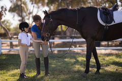 Full length of female jockey with sister feeding horse. While standing on field at paddock Royalty Free Stock Images