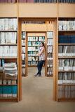 Full length of a female student standing in the library Stock Images