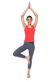 Full length of a fit smiling woman standing in tree pose Stock Images