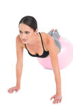 Full length of a fit woman doing push ups on fitness ball Royalty Free Stock Photo